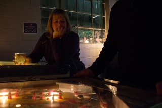 "Englewood, Colo. – April 22, 2017 – Joan Heller looks on as her boyfriend Mike Friednash answers the buzzers and bells during a competitive pinball match at Devil's Head Distillery. ""The trick,"" says Friednash, ""is to focus on the silver ball, and ignore the trash talk coming from your opponent."" (Derek Gregory)"